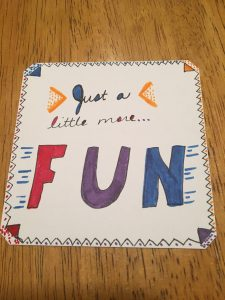 Square white card with hand lettering that reads 'Just a little more fun.'