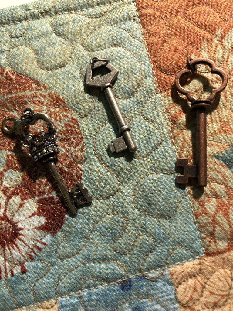 Three small decorative keys are resting on a quilted mat.