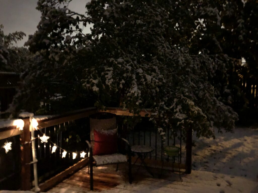 A backyard deck, set up for summer, is covered in snow.